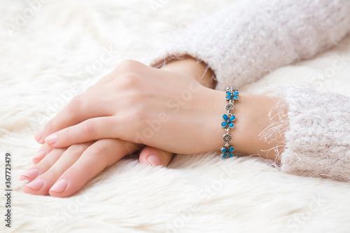 Fototapeta Flower bracelet on young woman hand wrist on white, fluffy fur blanket