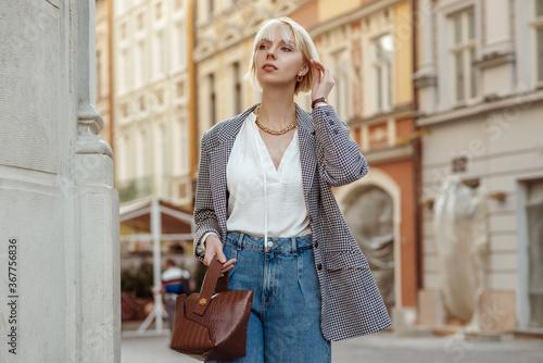 Carta da parati Street fashion photo of elegant  woman wearing trendy white blouse, stylish checkered blazer, high waist jeans, holding brown faux croco leather textured bag