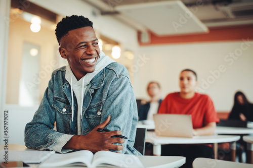 Canvas Print Smiling male student sitting in university classroom