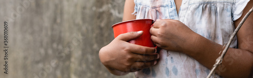 Canvas Print Panoramic crop of poor african american child holding metal cup on urban street