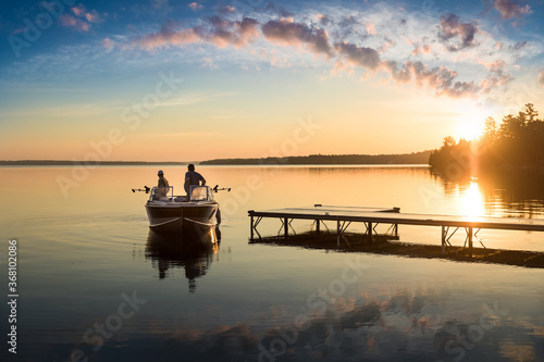 Fotografiet Cottage Life - Father and son fishing on a boat at sunrise/sunset at the peacefu