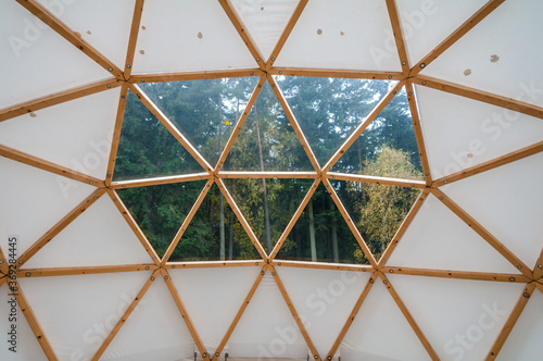 Fotografering Interior of large geodesic wooden dome tent with window and view to forest