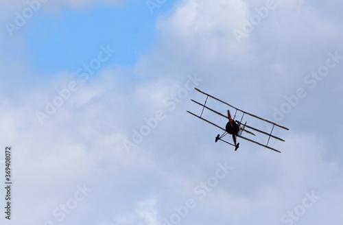 Obraz na płótnie Vintage  Sopwith Triplane in flight with clouds and blue sky.