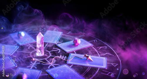 Fotografia Cartomancy - Pendulum On Blurred Altar With Defocused-Tarot Cards And Smoke
