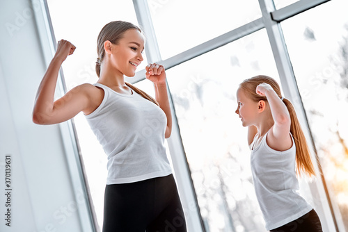 Mother and daughter showing strong hands in gym фототапет