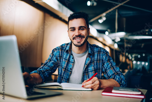 Canvas Print Portrait of cheerful male student enjoying learning in coworking office using laptop computer for research,happy freelancer looking at camera during making project for remote job making notes