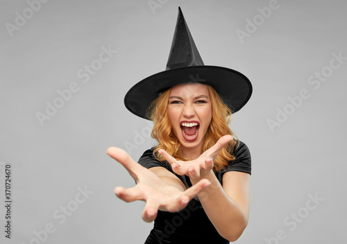 holiday, theme party and black magic concept - scary woman in halloween costume Fototapeta