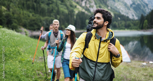 Group of friends hiking together outdoors exploring the wilderness and having fu Fototapeta