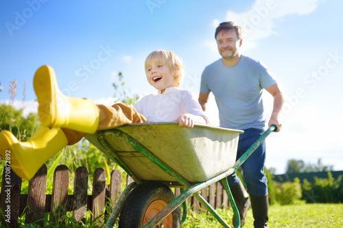 Happy little boy having fun in a wheelbarrow pushing by dad in domestic garden on warm sunny day Fotobehang
