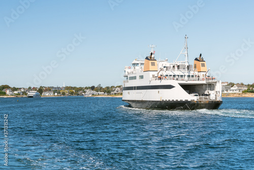 Canvas Print Huge car ferry sailing into a harbour on a clear autumn day