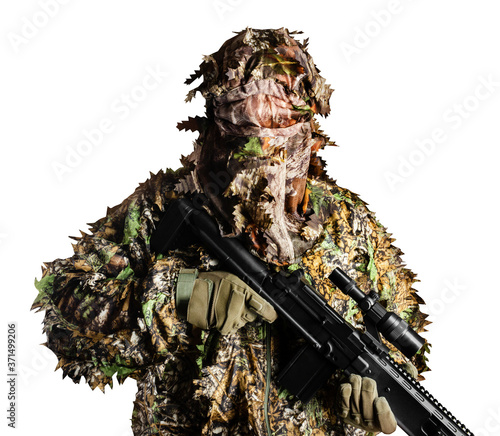 Fotografie, Obraz Isolated soldier in camouflaged masking forest leafs suit with rifle