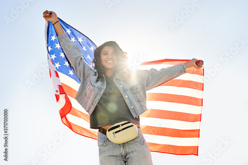 Smiling young African woman holding usa flag dancing under sunny sky looking at camera Fototapet