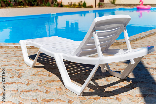 Fotografering Empty plastic white deck chairs near the swimming pool