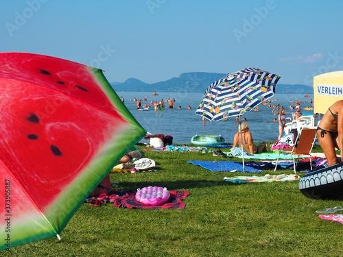 Obraz na plátně Balatonmáriafürdő, Hungary - July 29, 2020: Colorful umbrellas, sunbathing and b