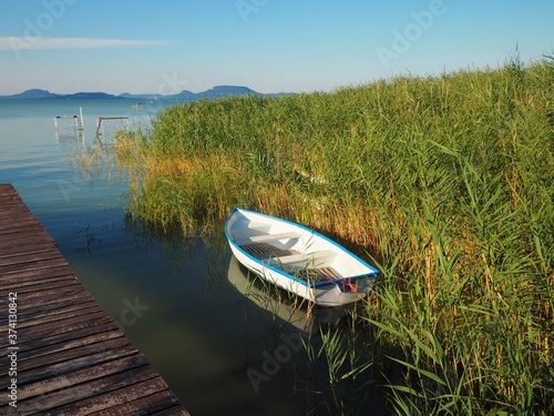 Fotografie, Obraz White wooden boat next to the reeds and beach expiring at the southern shore of