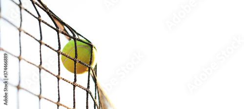 Canvas Print Bright greenish yellow tennis ball hitting the net.