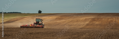 Photo one modern tractor with a trailed disc harrow works a wide hilly field before sowing