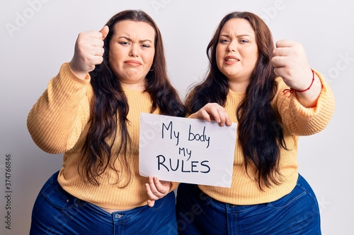 Fototapeta Young plus size twins holding my body my rules banner annoyed and frustrated sho
