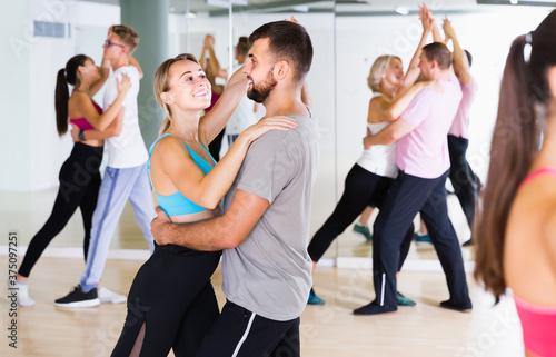 Billede på lærred Dancing positive russian couples learning salsa at dance class