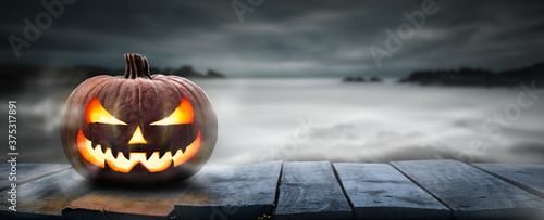 Fotografiet One spooky halloween pumpkin, Jack O Lantern, with an evil face and eyes on a wooden bench, table with a misty gray coastal night background with space for product placement