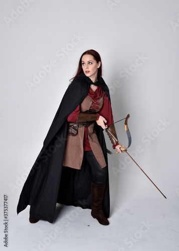 Photo Full length portrait of girl with red hair wearing medieval archer costume with black cloak