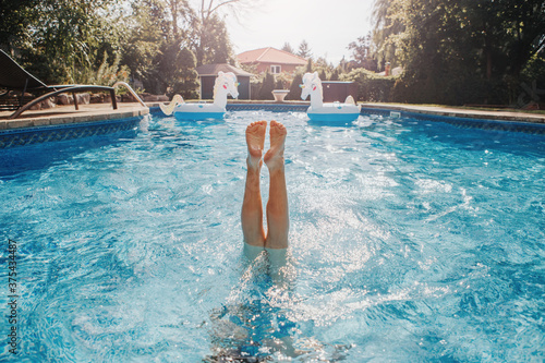Photo Funny child diving in swimming pool on home backyard