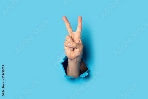 Male hand makes a two fingers up greeting gesture on a blue background Fototapeta