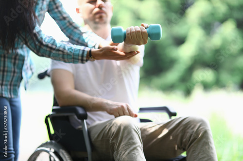 Man in wheelchair sits and holds dumbbell in his hand Fototapet