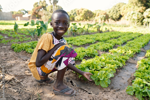 Canvas Print Food for Africa! Young Black Boy Smiling in front of Lettuce Salad Field