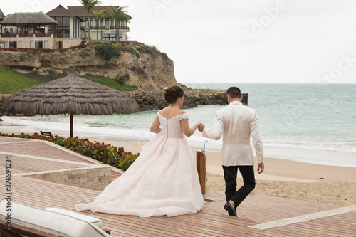 Wallpaper Mural Latino Bride and groom with white tuxedo walking while holding hands at the beac