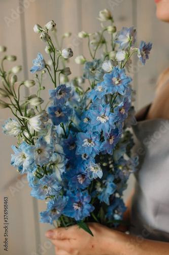 Photo woman holding bouquet of flowers delphinium
