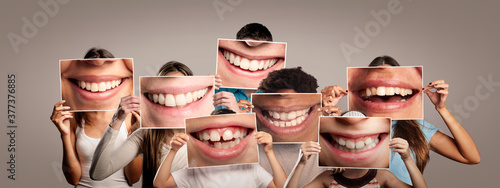 Photo group of happy people holding a picture of a mouth smiling on a gray background