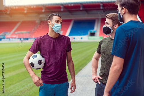 Canvas Print Soccer players in football stadium during covid-19 wearing masks