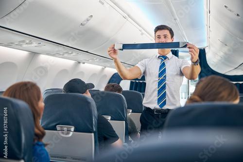 Obraz na plátne Handsome steward training safety prior procedures to flight take off