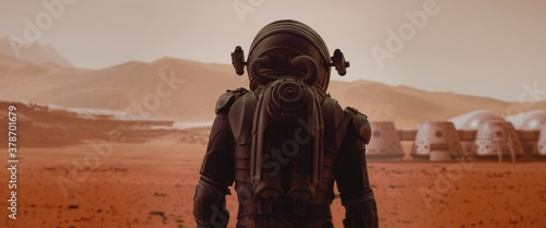 Fotografia Back view of astronaut wearing space suit walking on a surface of a red planet