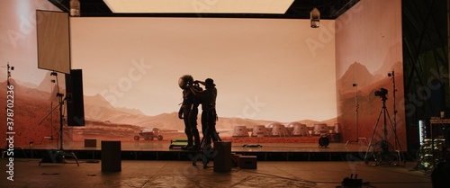 Photo Behind the scenes shot of virtual production stage with huge LED screens, cinematorgapher shooting Mars scene