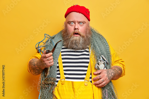 Photo Plump bearded professional man mariner stares at camera with displeased shocked expression holds smoking pipe and goes fishing isolated on yellow background