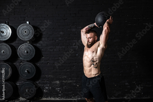 Fényképezés Young sweaty strong muscular fit man with big muscles doing ball throwing on the