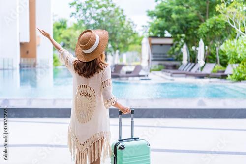 Valokuva Young woman traveler enjoying a summer vacation at swimming pool in tropical res