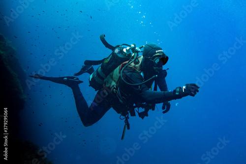 Wallpaper Mural Scuba diver swimming in deep blue