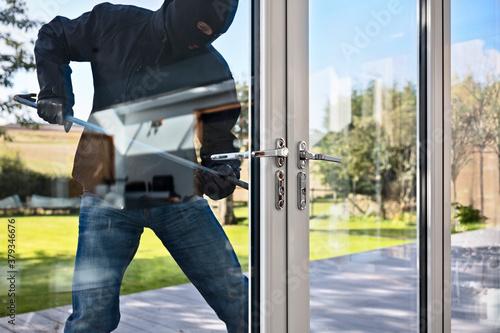 Wallpaper Mural Burglar breaking into a house via a window with a crowbar