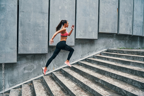 Photo Full length of young woman in sports clothing jogging while exercising on the st