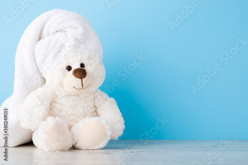 Smiling, lovely white teddy bear sitting on shelf at light blue wall. Towel on head. Closeup. Children bathing concept. Pastel color. Empty place for text. Front view.