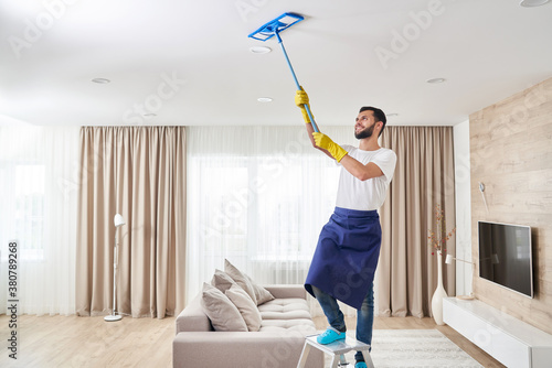 Carta da parati Man cleaning ceiling and lamps in living room