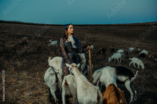 Fotografie, Tablou Woman farmer stands with pitchfork among a herd of goats.