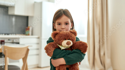A little girl embracing a fluffy brown teddy bear looking into a camera