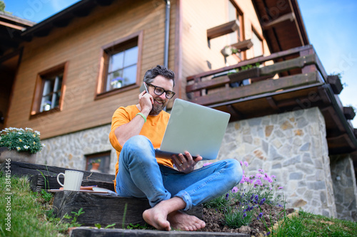 Mature man with laptop and smartphone working outdoors in garden, home office concept.