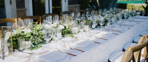 Photographie Wedding banquet with clear glass goblets and wine glasses, white plates and gold