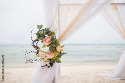 Photo Wedding bamboo gazebo, decorated with tropical flowers and coloured fabrics on t