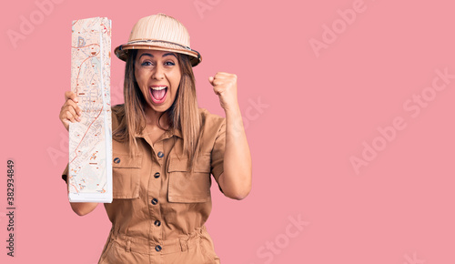 Fotografia Young beautiful woman wearing explorer hat holding map screaming proud, celebrat